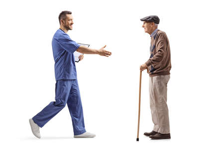 Medical worker greeting with hand an elderly man with a walking cane isolated on white background 版權商用圖片