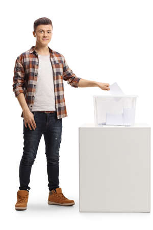 Full length portrait of a young man putting a vote in an election box and looking at the camera isolated on white background Foto de archivo