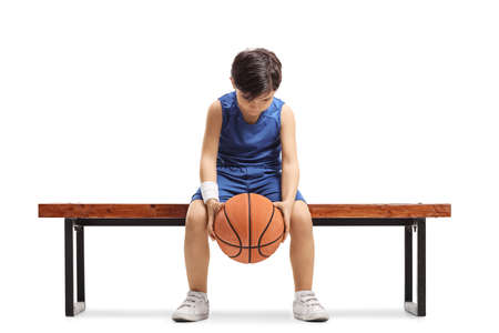 Sad little boy sitting on a bench with a basketball isoalted on white background Stock fotó