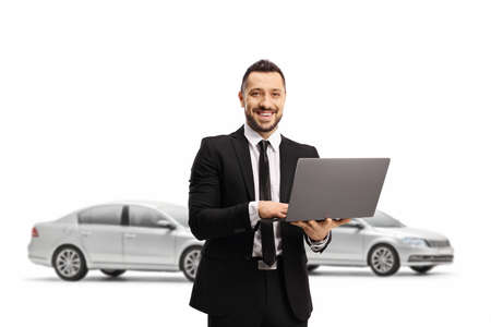 Man in a suit with a laptop computer smiling at the camera and posing in front of cars isolated on white background Stockfoto