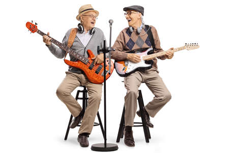 Cheerful elderly men sitting on chairs playing guitars and singing isolated on white background