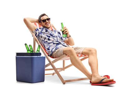 Tourist with a bottle of beer on a deckchair with a cooling box beside him isolated on white background