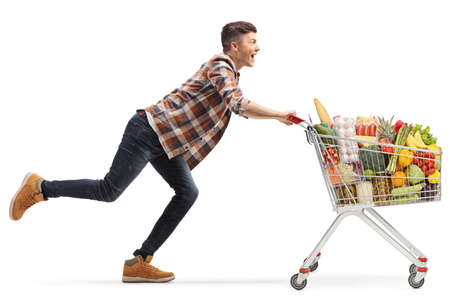 Happy young man running with a full shopping cart isolated on white background