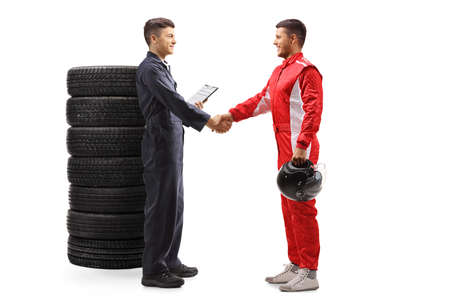 Full length profile shot of an auto mechanic shaking hands with a professional racer isolated on white background
