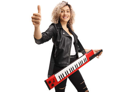 Woman with a red keytar synthesizer showing a thumb up sign isolated on white background