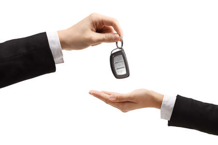 Male hand giving car keys to a female hand in a formal wear isolated on white background Foto de archivo