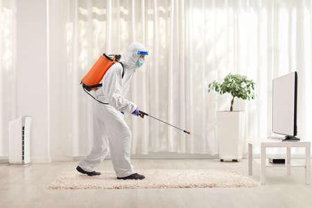 Man in a hazmat suit sanitising a room in an apartmemt
