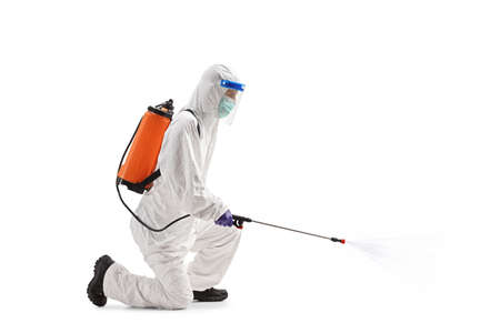Man in a hazmat suit kneeling and sanitising with disinfectant isolated on white background