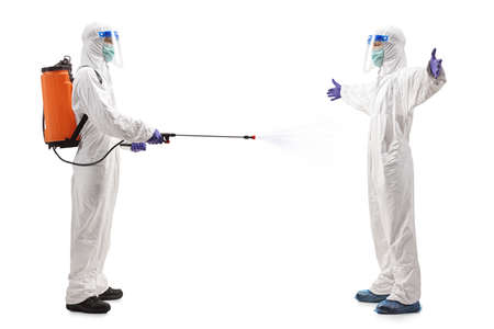 Full length profile shot of a specialist in a hazmat suit disinfecting another man in a hazmat suit isolated on white background