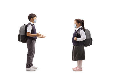 Full length profile shot of a schoolboy talking to a schoolgirl with protective face masks isolated on white background