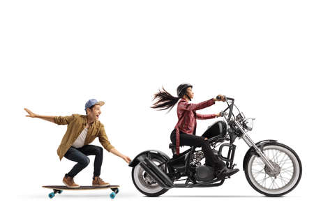 Full length profile shot of a woman riding a chopper and pulling a guy on a skateboard isolated on white background