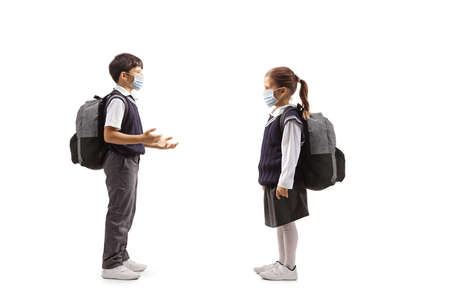Full length profile shot of a schoolboy talking to a schoolgirl both wearing face masks isolated on white background