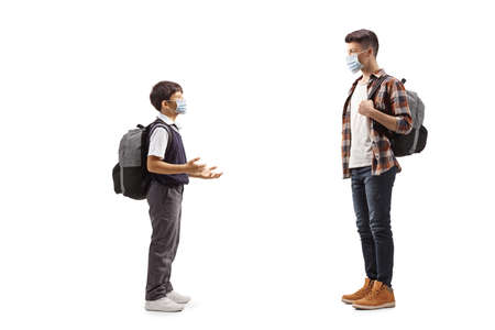 Full length profile shot of a schoolboy talking to a teen boy with protective face masks isolated on white background 写真素材