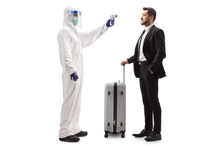 Full length profile shot of a man in a hazmat suit measuring temperature to a man with a suitcase isolated on white background