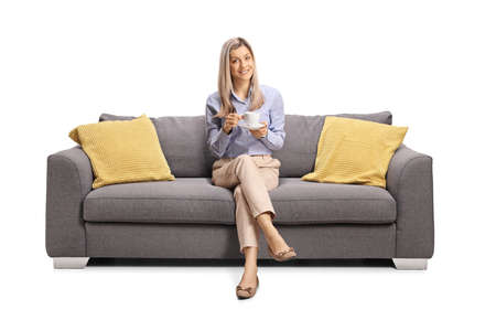 Young woman sitting on a couch with a cup of coffee isolated on white background