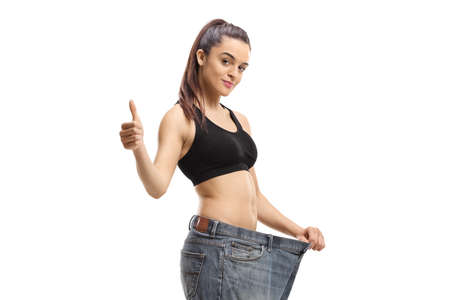 Young woman wearing pair of big size jeans and showing thumbs up isolated on white background