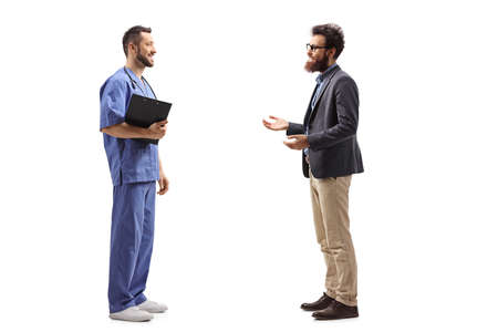 Full length profile shot of a bearded man talking to a male doctor in a blue uniform isolated on white background 免版税图像