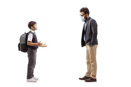 Full length profile shot of schoolboy explaining something to a bearded man and wearing face masks isolated on white background
