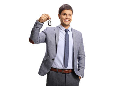 Guy in formal clothing holding a car key isolated on white background