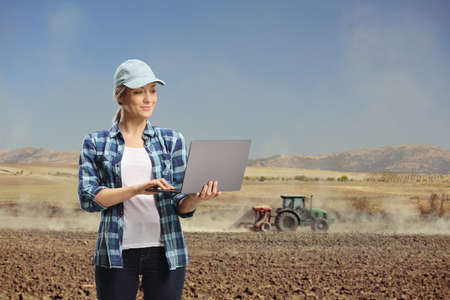 Young woman with a laptop computer standing on a field with a tractor operating on the soil
