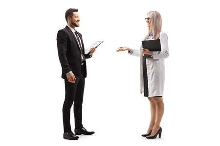 Full length profile shot of a female doctor talking to a professional man in a black suit isolated on white background Standard-Bild