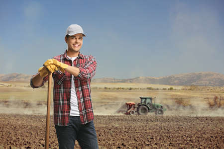 Male worker in a field with a tractor cultivating the soil in the back on a sunny day