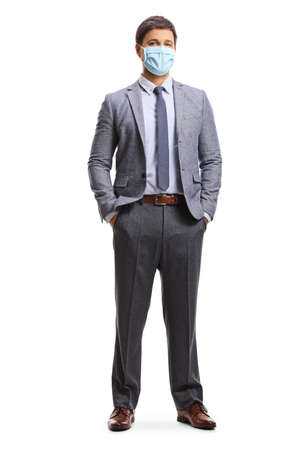 Full length portrait of a young man in corporate wear wearing a protective face mask isolated on white background Imagens