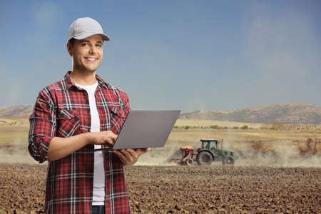 Agricultural engineer in a field with a laptop computer and a tractor plowing the soil