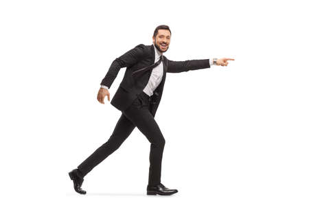 Handsome man in a black suit running and pointing isolated on white background Stock fotó