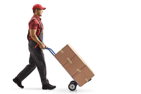 Full length profile shot of a male worker pushing boxes on a hand-truck isolated on white background