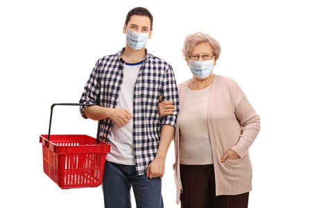 Young man with an empty shopping basket and an elderly woman wearing protective face masks isolated on white background