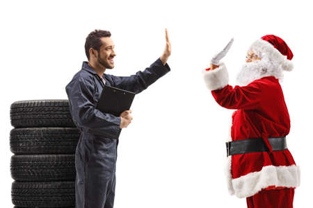 Auto mechanic with a pile of tires gesturing high five with Santa Claus isolated on white background Stock Photo