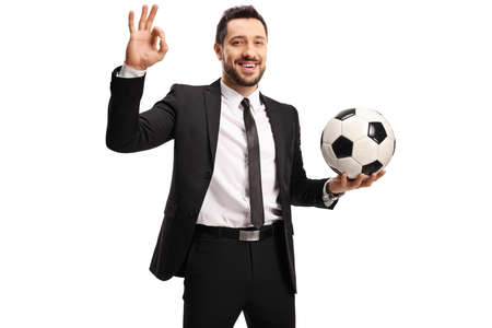 Man in a black suit holding a soccer ball and gesturing ok sign isolated on white background