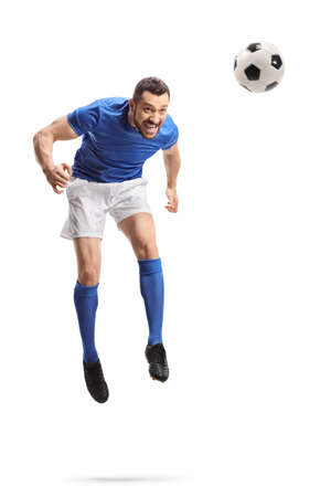 Full length portrait of a footballer jumping and hitting a ball with head isolated on white background