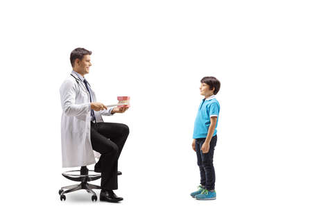 Male dentist showing theeth brushing with a model jaw to a boy isolated on white background