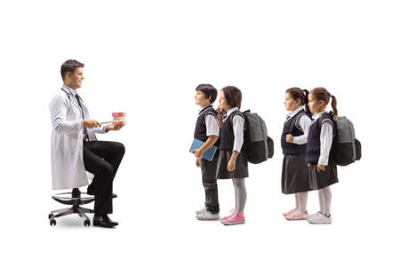 Dentist showing theeth brushing with a model jaw to a group of schoolchildren isolated on white background
