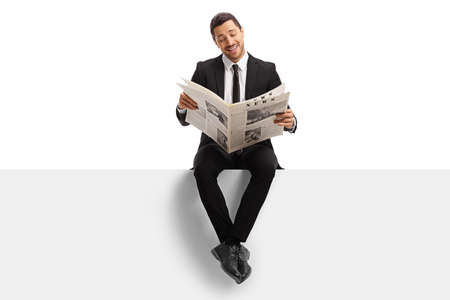 Young buisnessman sitting on a blank panel and reading a newspaper isolated on white background Stockfoto