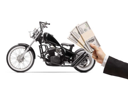 Male hand in front of a custom choper motorbike holding stacks of us dollar money isolated on white background Foto de archivo