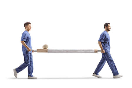 Full length profile shot of two male healthcare workers carrying an empty stretcher bed isolated on white background