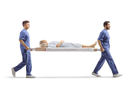 Full length profile shot of healthcare workers carrying a female patient on a stretcher isolated on white background Stockfoto