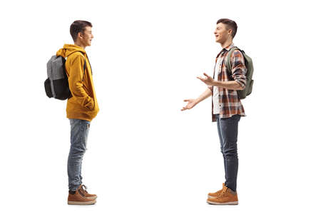 Full length profile shot of two male teenage students having a conversation isolated on white background