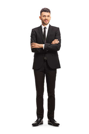 Full length portrait of a young businessman posing with crossed hands isolated on white background Foto de archivo
