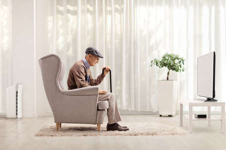 Sad lonely elderly man sitting in an armchair at home