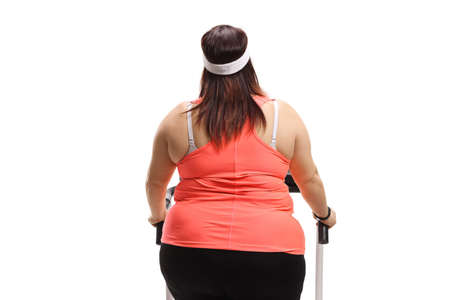 Rar view of an overweight woman on a treadmill isolated on white background