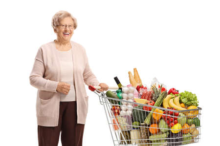 Elderly woman posing with a shopping cart isolated on white background
