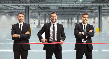 Businessmen cutting a red ribbon tape and opening a factory hall