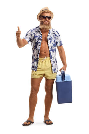 Full length portrait of a bearded young man in swimming shorts holding a portable fridge and showing thumbs up isolated on white background