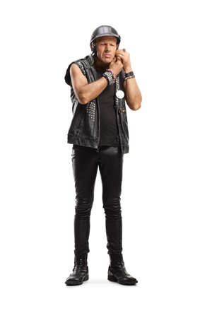 Full length portrait of a biker in a leather vest putting on a helmet isolated on white background