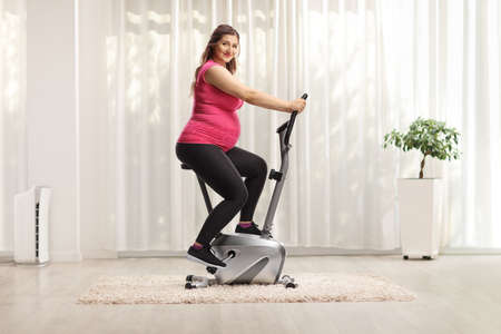 Pregnant woman in a pink top riding an exercise bike at home and looking at camera