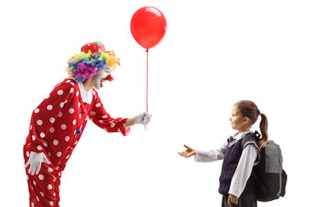 Cheerful clown giving a red balloon to a schoolgirl isolated on white background Reklamní fotografie